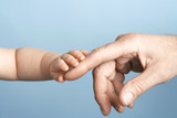 Baby and Man touching hands, close-up on hands