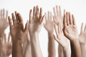 Young men and women raising hands, close-up of hands