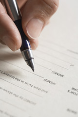 Man signing document, close up of pen in hand