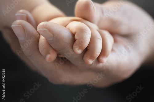 Baby holding man's finger, close up of hands