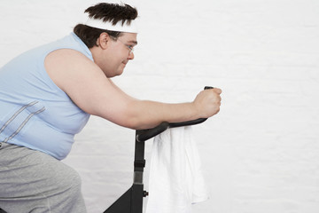 Overweight man on Exercise Bike, side view