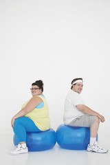 Overweight man and woman sitting back to back on exercise balls, portrait