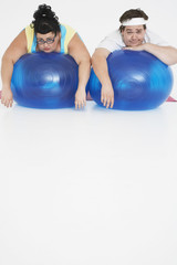 Overweight man and woman lying on Exercise Balls, portrait, front view