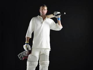 Cricket player, standing holding cricket bat on shoulder