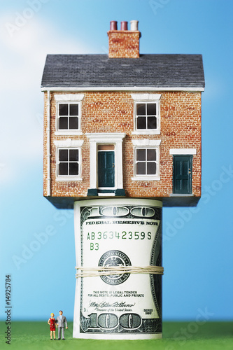 Model house on roll of $100 notes