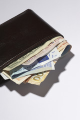Wallet full of different currencies, in studio