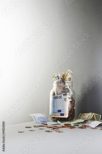 Notes and coins overflowing from jar