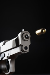 Gun shooting bullet on black background, close up