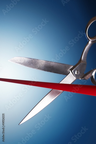 Scissors cutting red ribbon in studio
