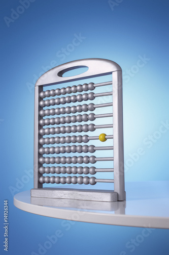 Single yellow bead on silver abacus in studio