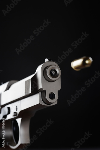 Gun shooting bullet on black background, close up