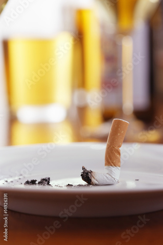 Cigarette in ashtray on table with glasses of beer