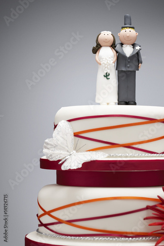 Comical bride and groom figurines on top of wedding cake