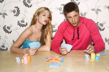Young Couple sitting on sofa playing cards, woman looking at cards of man
