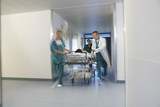 Doctors running Patient on gurney through hospital corridor, motion blur