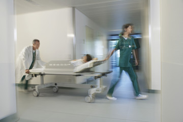 Medical Workers Moving Patient on gurney through hospital corridor, motion blur