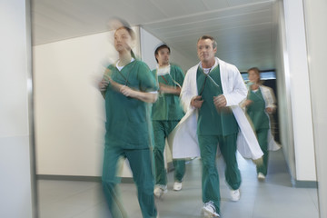 Motion blur image of small group of doctors and nurses in scrubs running through hospital corridor