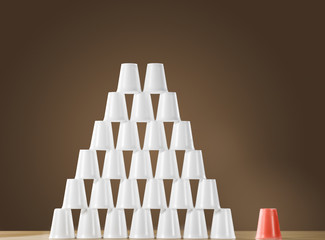 Pyramid of white plastic cups on table next to single red cup