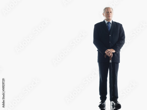 Middle-aged businessman leaning on umbrella