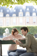 Young couple reading guide book, sitting on bench in park