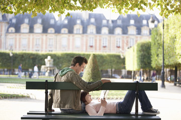 Young couple reading book, sitting on bench in park