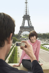 France, Paris, Man photographing woman in front of Eiffel Tower