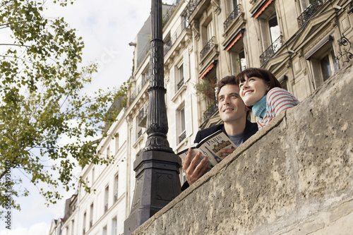 France, Paris, Couple looking over bridge with guidebook