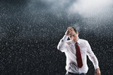Businessman running hands through wet hair, standing in the Rain