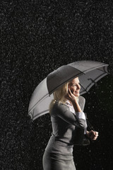 Businesswoman standing under umbrella, talking on mobile