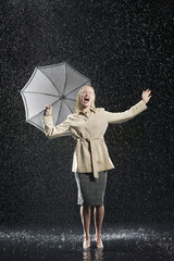 Woman standing in overcoat, holding umbrella, singing in the rain