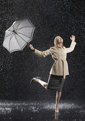 Woman standing on one leg, holding umbrella, leaning into falling rain