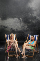 Sunbathers sitting in sunloungers during downpour