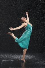 Woman standing on one leg, leaning into falling rain