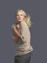 Woman with hair blowing, arms crossed, side view