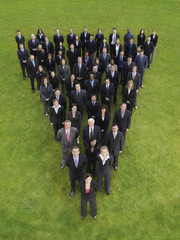Large group of business people standing in triangle formation, elevated view
