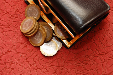 coins and a purse on a red background