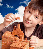 Boy building house against the blue sky poster