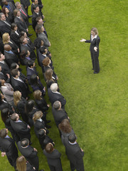 Business woman facing large group of business people in formation, elevated view