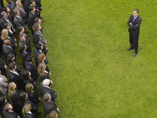 Business man facing large group of business people in formation, elevated view