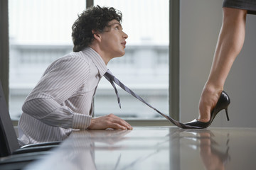 Businesswoman standing on desk stepping on businessman's tie, side view