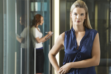 Businesswoman standing in office corridor, portrait