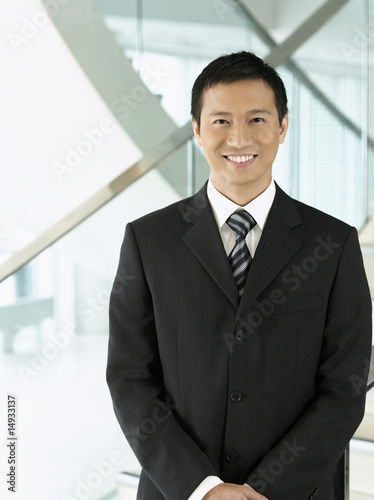 Confident Businessman standing, hands clasped