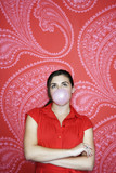 Teenaged girl blowing bubble against pink and red patterned wallpaper