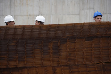 Construction workers behind a stack of rebar