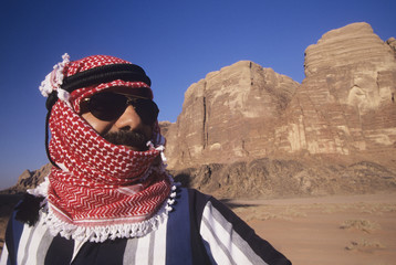 Arab Man in turban, Wearing Sunglasses, standing in desert landscape
