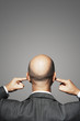 Balding businessman with fingers in ears, back view