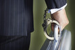 Middle-aged businessman handcuffed to briefcase, mid section, close-up, back view