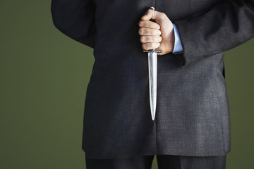 Mid-adult businessman standing, holding knife behind back, mid section, back view