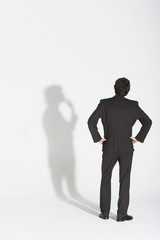 Young businessman standing, hands on hip, arguing with own shadow, back view