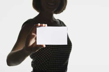 Smiling, silhouetted woman standing, holding large blank card, mid section